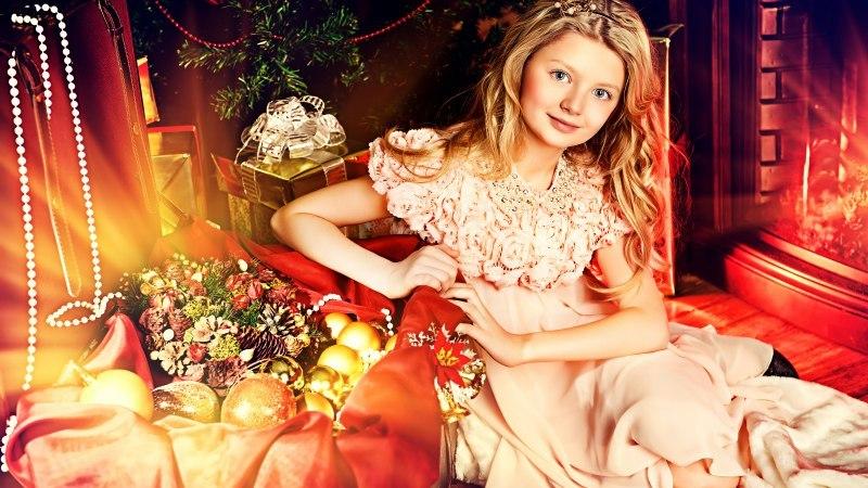 sidit_shary_podarki_u_kamina_devushka Новогодние платья для девочек от 3 до 12 лет: праздничные образы на Новый Год, в садик